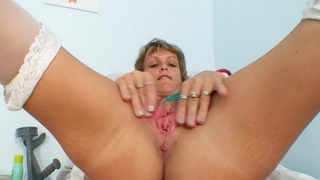Skinny cougar gray nurse toys her piss hole on gynochair